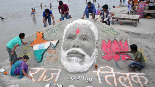 College students making a sand sculpture of Narendra modi in Allahabad.