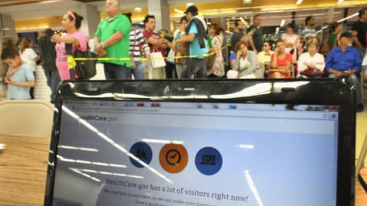 People wait in line to see an agent from Sunshine Life and Health Advisors as the Affordable Care Act website is reading, 'HealthCare.gov has a lot of visitors right now!' at a store setup in the Mall of Americas on March 31, 2014 in Miami, Florida.