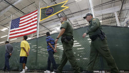 Detainees are escorted as hundreds of mostly Central American children are being held at a U.S. Customs and Border Protection center in Nogales, Ariz., on June 18, 2014.