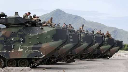U.S. marines of 1st Battalion, 8th Marines Regiment sit on their Amphibious Assault Vehicles (AAV) while waiting for a go signal to roll into the water facing the South China Sea during the Cooperation Afloat Readiness and Training (CARAT) Philippines 2014, a U.S.-Philippines military exercise, at San Antonio, Zambales north of Manila June 30, 2014.
