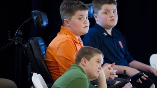 Jack Willis, center, Nolan Willis, right, and Max LeClaire,bottom, are all afflicted with Duchenne muscular dystrophy. They attended the opening for Sarepta Therapeutics new global headquarters in Cambridge on Monday morning, June 2, 2014.