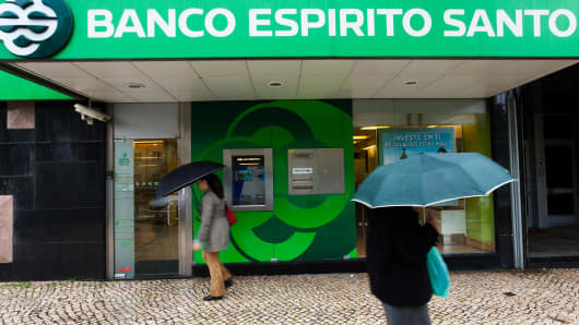 Pedestrians carry umbrellas past an Banco Espirito Santo SA branch in Lisbon, Portugal.