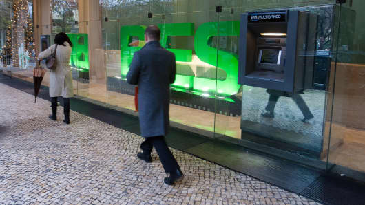 Pedestrians pass an ATM outside the headquarters of Banco Espirito Santo SA, Portugal's biggest publicly traded bank, in Lisbon, Portugal.