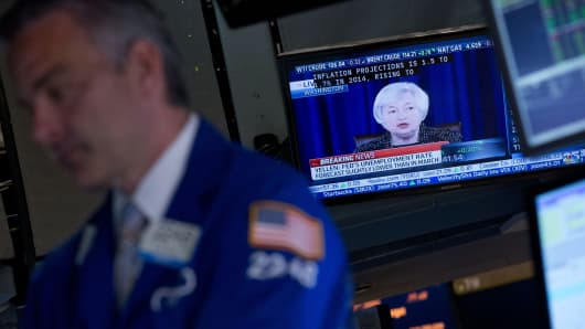 A trader works on the floor of the New York Stock Exchange during a press conference with Janet Yellen.