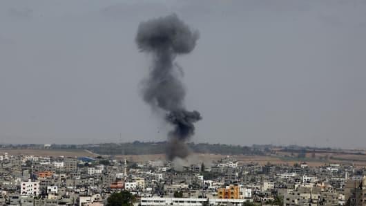 Smoke rises following an Israeli missile strike on the Gaza Strip on July 13, 2014.