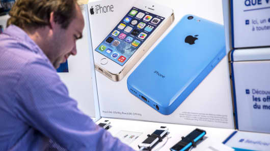 A customer looks at a display for the Apple iPhone 5c and iPhone 5s in Paris, July 3, 2014.