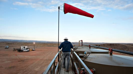 An employee of Kodiak Oil & Gas Corp., walks along a catwalk at the top of crude oil storage tanks outside Watford City, North Dakota, Feb. 14, 2012.