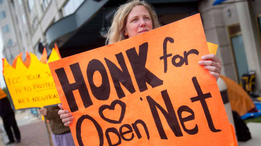 A demonstrator holds a sign in support of net neutrality outside the Federal Communications Commission headquarters in Washington, May 14, 2014.