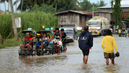 Residents cross a flooded road on July 15, 2014 in Sultan Kudarat, Mindanao, Philippines.
