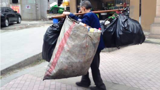 Elderly man collecting garbage for recycling in Chengdu, Sichuan Province, China.