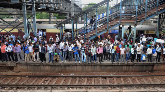 Indian commuters crowd onto a platform as they wait for a train at a station on the suburban train network in Mumbai.