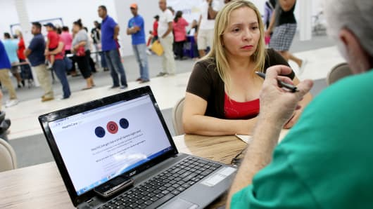 Norma Licciardello sits with an agent from Sunshine Life and Health Advisors as she tries to purchase a health insurance plan at a store setup in the Mall of Americas in Miami.