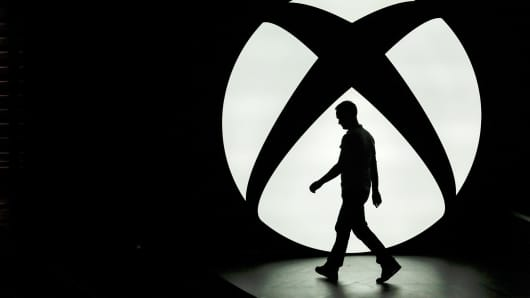 A man walks past the Microsoft Xbox One logo during a media event ahead of the E3 Ele