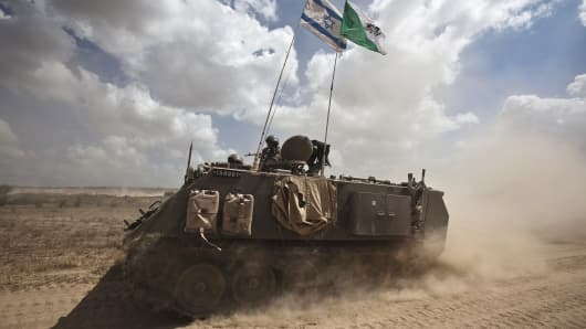 Israeli soldiers ride on an armored personnel carrier outside the Gaza Strip.
