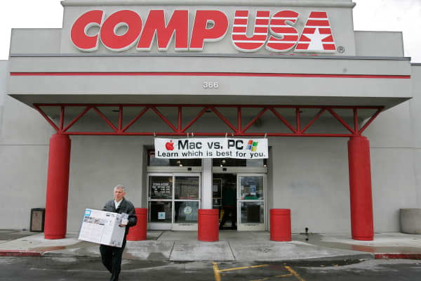 A customer walks out of a CompUSA store in Orem, Utah on Wednesday, April 5, 2006, as a sign reading 'Mac vs. PC' is seen hanging out front.