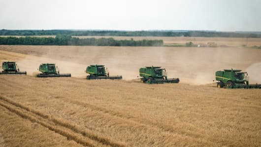 Combine harvesters drive across a wheat field during a summer harvest in Poltava region, Ukraine, on Friday, July 18, 2014.