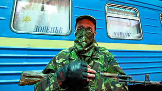An armed pro-Russian separatist stands guard at a railway station in Donetsk July 21, 2014.