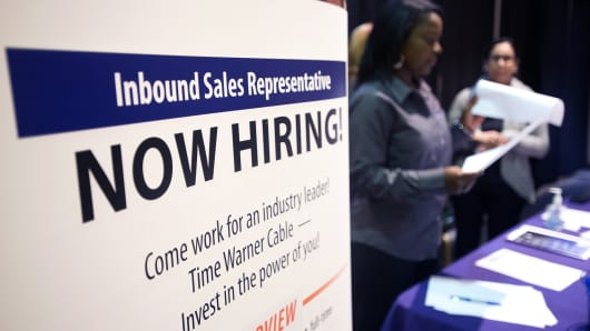 "A ""Now Hiring"" sign stands at an exhibitors' table at the Columbus Career Fair in Columbus, Ohio."