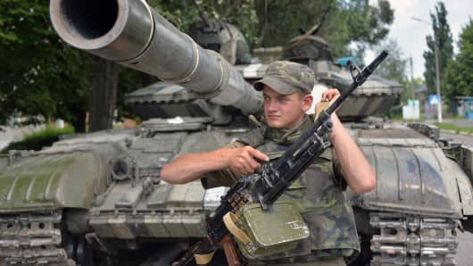 A Ukrainian serviceman guards in front of a tank in the small eastern city of Seversk on July 12, 2014, a day after the city was freed from pro-Russian militants.