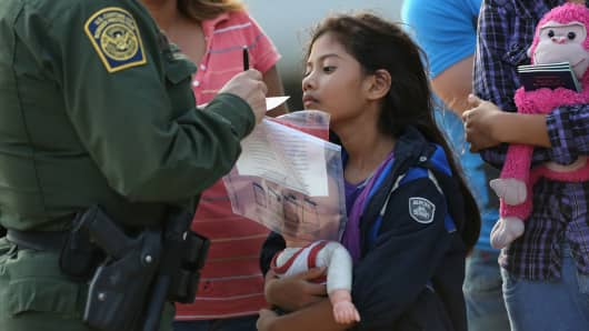 Salvadorian immigrant Stefany Marjorie, 8, watches as a U.S. Border Patrol agent records family information on July 24, 2014 in Mission, Texas. Like most of the recent surge of Central American immigrant women and children, her family brought documents, often birth certificates, to prove their nationality to U.S. Border officials.