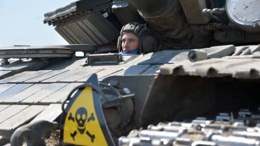 A Ukrainian service man looks out from a tank, part of a convoy of vehicles of the Ukrainian forces driving towards the eastern Ukrainian city of Lysychansk, in the region of Lugansk, on July 25, 2014.