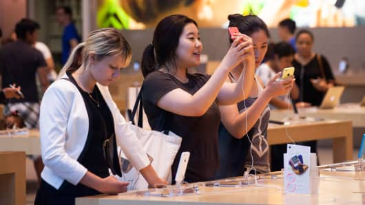 Shoppers look at iPhones in the Apple store on Manhattan's Upper West Side in New York, July 20, 2014.