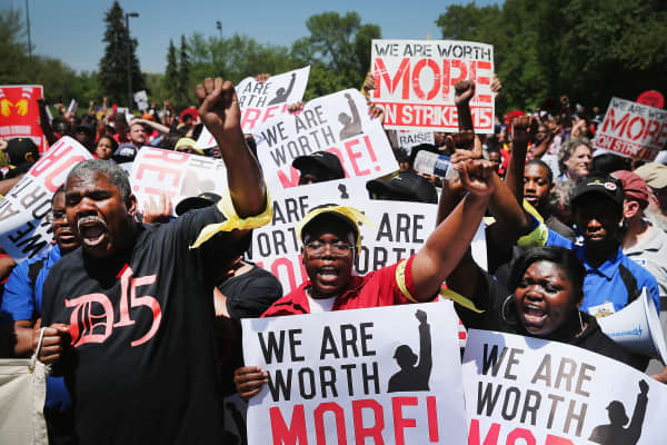 Fast food workers and activists demonstrate outside the McDonald's corporate campus on May 21, 2014 in Oak Brook, Illinois.