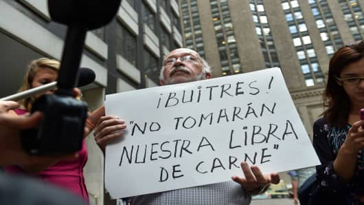 Protestor Francisco Sobrero holds a sign that translates as 'Vultures! Don't take our pound of meat' outside the office building of mediator Daniel Pollack July 30, 2014 in New York.