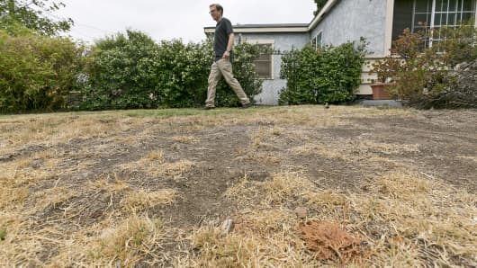 Michael Korte walks on the brown lawn in front of his home in Glendora, Calif.