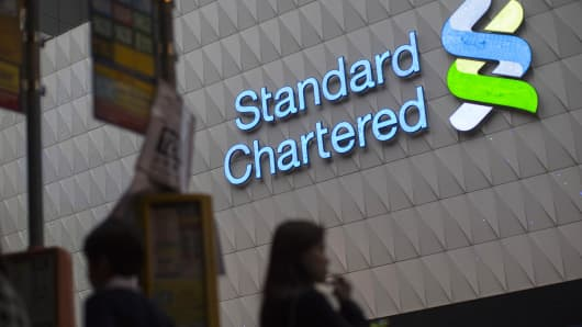 A Standard Chartered sign is displayed on a Standard Chartered Bank branch, in Hong Kong, March 3, 2014.