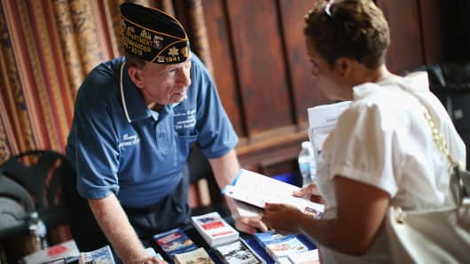 Barry Cicero, left, with the American Legion discusses oportunities for veterans with U.S. Army veteran Risa Stegall at the Hiring Our Heroes job fair for veterans at the University of Chicago on July 30, 2014 in Chicago.