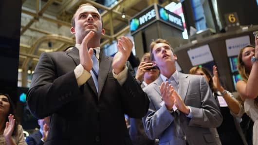 Guests applaud at the closing bell of the New York Stock Exchange in New York.