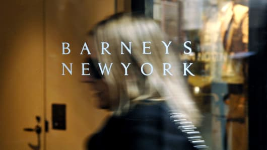 A Barneys New York logo is pictured as a woman enters their 5th Avenue store in New York.