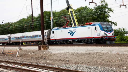 A new Siemens-built Amtrak Cities Sprinter locomotive passes work crews in Hamilton, N.J., where a new substation and catenary system will support future high-speed rail.