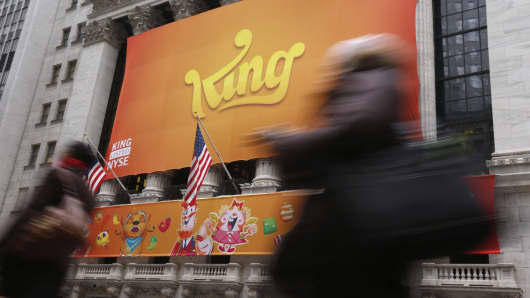 Pedestrians walk past a King Digital Entertainment banner on the facade of the New York Stock Exchange in New York.