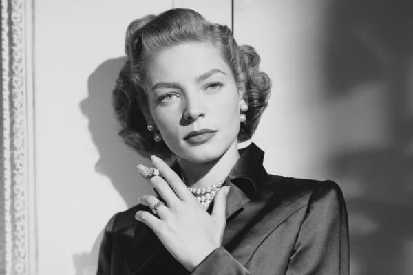 1950: American screen star Lauren Bacall wearing a dark satin suit for her role as Amy North in 'Young Man with a Horn'.