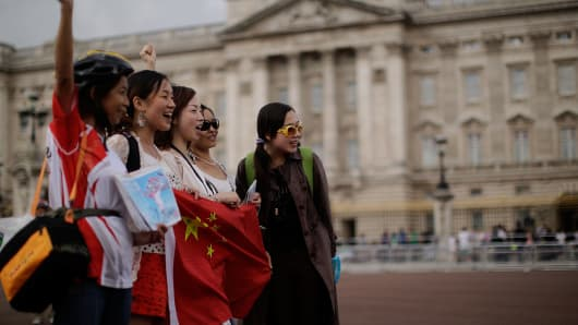Chinese tourists have their pictures taken outside Buckingham Palace on July 29, 2012 in London, England.