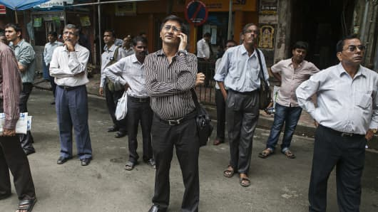Men looks up at an electronic screen displaying stock figures at the Bombay Stock Exchange (BSE) in Mumbai, India.