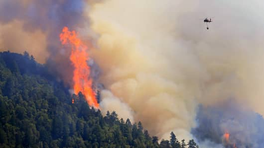 An Air National Guard helicopter moves in to make a water drop as the Lodge Fire between Legget and Laytonville jumps the Eel River and moves upslope, Friday Aug. 8, 2014.