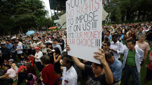 A man holds up a placard during the 'Return Our CPF' protest at the Speakers' Corner at Hong Lim Park in Singapore.