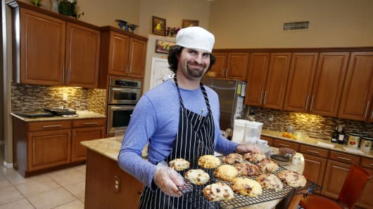Matt Cottle, owner of Stuttering King Bakery, smiles as he holds a tray of his scones in his parents' kitchen in Scottsdale, Ariz.