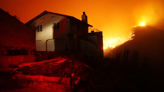 Fire fills a canyon behind a partially burned house in the mountains overlooking Montecito, south of Santa Barbara, Calif.