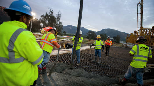 Construction workers pour concrete as part of the Caltrans Bridge expansion project to widen State Route 76 in San Diego County, Calif.