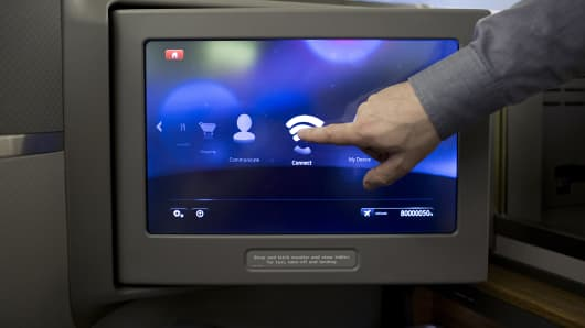An employee demonstrates wireless Internet capabilities on a screen in the first-class cabin aboard an American Airlines airliner at Hong Kong International Airport.