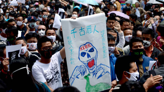 Demonstrators display banners during a protest against plans for a factory which will produce paraxylene (P