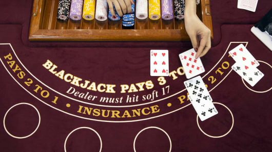 A croupier deals a card on a blackjack table inside the Venetian Macao resort and casino, operated by Sands China, in Macau, China.