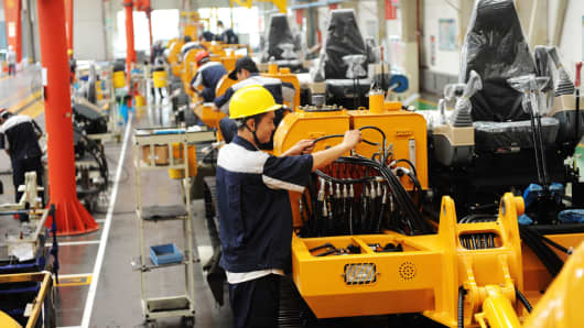 A scene of Chinese workers assembling machinery parts in a factory.