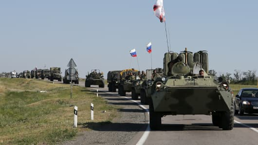 Russian military personnel ride atop armoured personnel carriers (APCs) outside Kamensk-Shakhtinsky, Rostov Region, August 15, 2014.