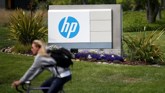 A cyclist rides by a sign outside of the Hewlett-Packard headquarters on May 23, 2014 in Palo Alto, Calif.