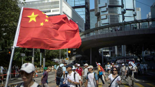 A anti-Occupy Central supporter carry a Chinese national flag during the march on August 17, 2014 in Hong Kong.